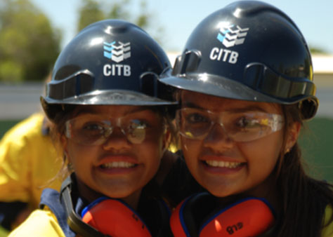 Image shows two girls wearing hard hats and smiling at the camera.